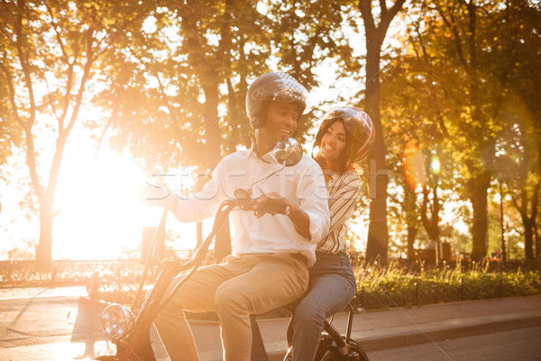 Carefree african couple rides on modern motorbike in park Stock photo © deandrobot