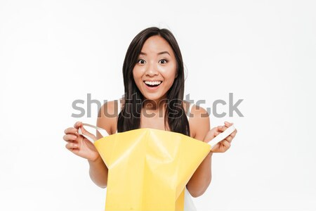 Portrait of a happy asian woman looking inside shopping bag Stock photo © deandrobot
