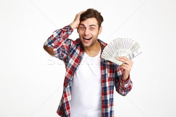 Portrait of a overwhelmed excited man holding bunch of money Stock photo © deandrobot