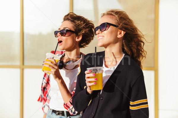 два улыбаясь Солнцезащитные очки питьевой апельсиновый сок Сток-фото © deandrobot