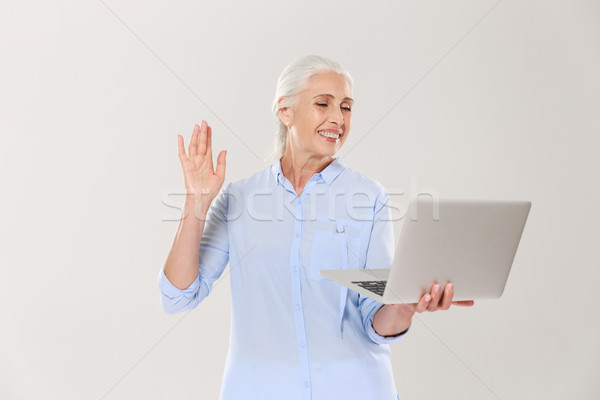 Funny mature woman using laptop computer isolated over white Stock photo © deandrobot