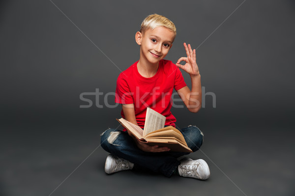 Cheerful little boy child reading book showing okay gesture. Stock photo © deandrobot