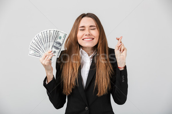 Happy lady with closed eyes holding dollars and making prey gesture isolated Stock photo © deandrobot