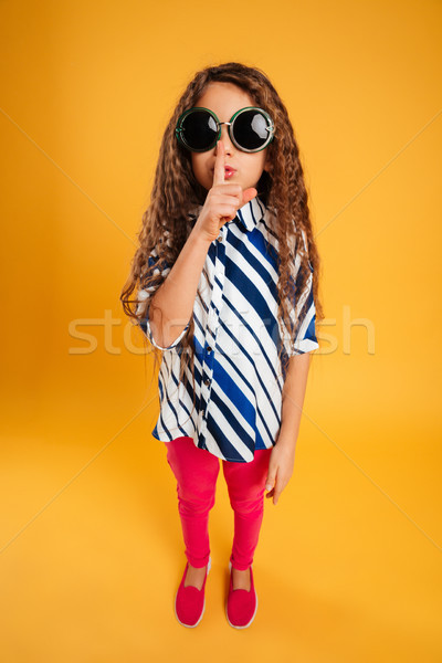 Little girl child wearing sunglasses showing silence gesture. Stock photo © deandrobot