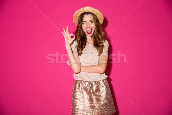 Excited young woman in hat showing okay gesture. Stock photo © deandrobot