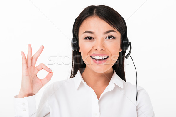 Close up of a cheerful asian woman in white shirt Stock photo © deandrobot