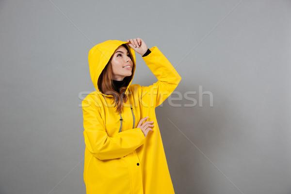 Portré boldog lány esőkabát pózol fej felfelé néz Stock fotó © deandrobot