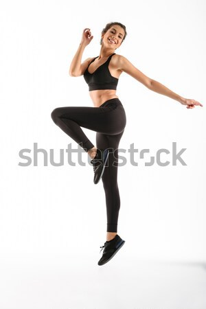 Full length image of Happy fitness woman jumping in studio Stock photo © deandrobot