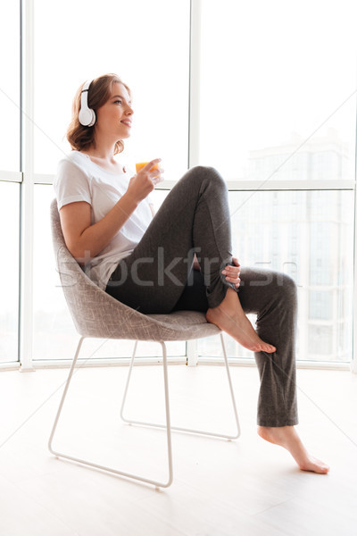Happy young woman sitting near window drinking juice Stock photo © deandrobot