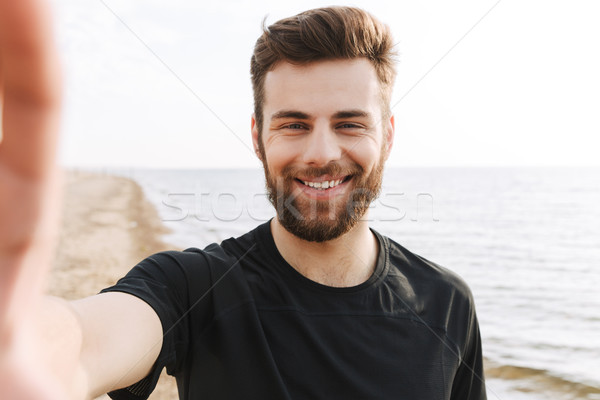 Cheerful young sportsman with headphones Stock photo © deandrobot