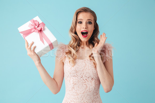 Surprised happy blonde woman in dress holding gift box Stock photo © deandrobot