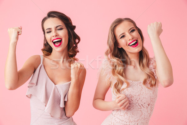 Two cheerful women in dresses rejoices and screaming together Stock photo © deandrobot
