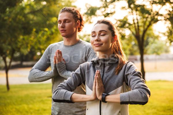 Fitness loving couple friends in park make meditate exercises. Stock photo © deandrobot