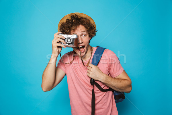 Stock photo: Photo of excited traveler man 18-20 with curly hair wearing back
