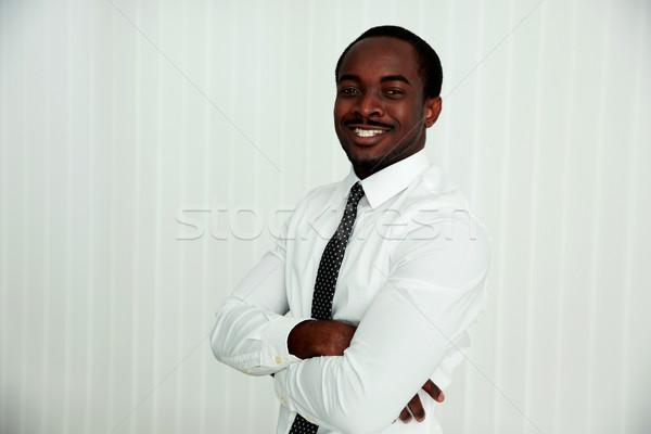 счастливым африканских бизнесмен оружия сложенный служба Сток-фото © deandrobot