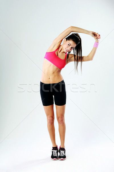 Young smiling sport woman stretching on gray background Stock photo © deandrobot