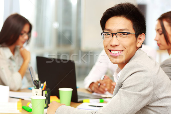 Portrait of happy businessman sitting in front of colleagues Stock photo © deandrobot