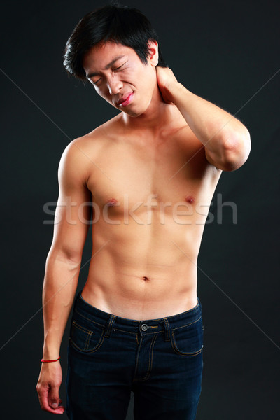 Asian man suffering from neck pain on black background Stock photo © deandrobot