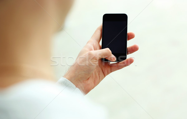 Closeup image of a man looking at blank smartphone display isolated on a white background Stock photo © deandrobot