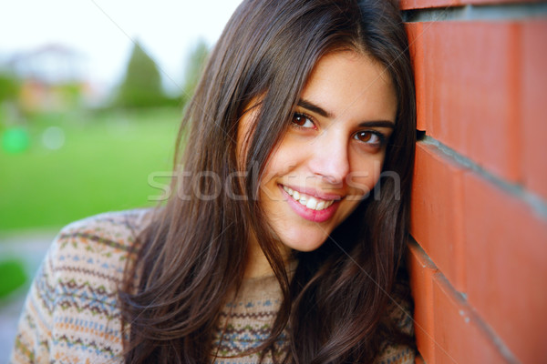 Beautiful cheerful woman standing near brick wall Stock photo © deandrobot