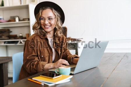 Young businesswoman sitting at desk and working. Smiling and looking back at camera Stock photo © deandrobot