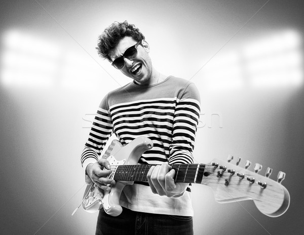 Musician is playing electrical guitar on stage Stock photo © deandrobot