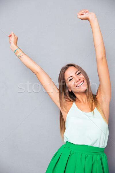 Mujer sonriente las manos en alto hasta retrato gris mirando Foto stock © deandrobot