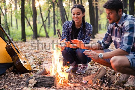 Couple reading for bonfire in the forest Stock photo © deandrobot