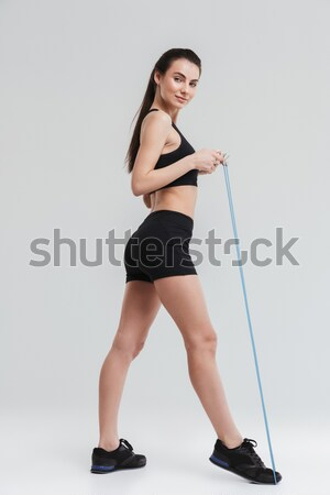 Young sportswoman on tiptoe with bottle of water Stock photo © deandrobot