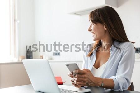 Happy female student using laptop in university Stock photo © deandrobot