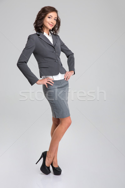 Full lenght portrait of young happy woman posing in formalwear Stock photo © deandrobot