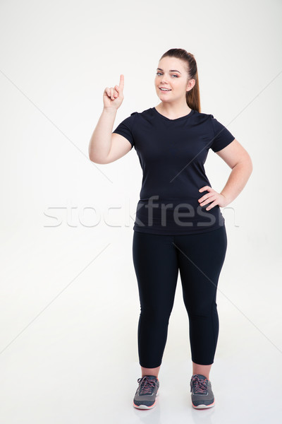 Happy fat woman in sports wear pointing finger up Stock photo © deandrobot