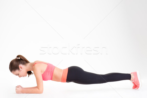 Beautiful focused fitness woman standing in a plank position  Stock photo © deandrobot