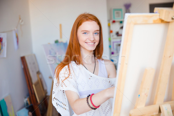 Cheerful attractive woman artist painting on canvas in art workshop Stock photo © deandrobot