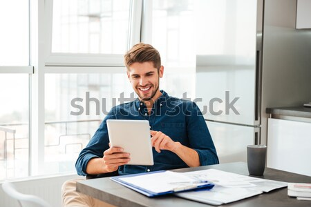 Happy designer working using pen tablet with stylus in office Stock photo © deandrobot