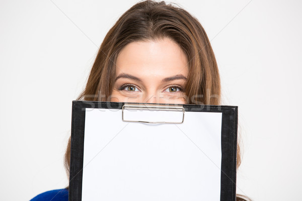 Cute lovely young woman hiding behind blank clipboard Stock photo © deandrobot