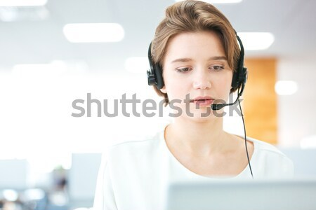 Serious pretty young woman working as support phone operator  Stock photo © deandrobot