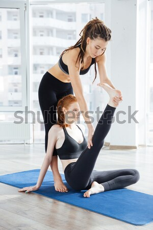 Focusedwoman doing split and stretching with trainer Stock photo © deandrobot