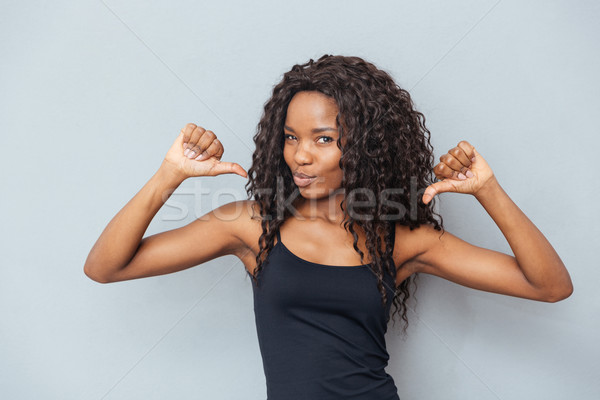 Afro american woman showing fingers at herself Stock photo © deandrobot