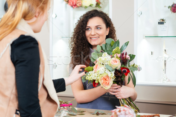 Smiling woman florist showing bouquet of flowers to customer Stock photo © deandrobot