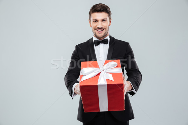 Cheerful attractive man in tuxedo giving you red gift box Stock photo © deandrobot