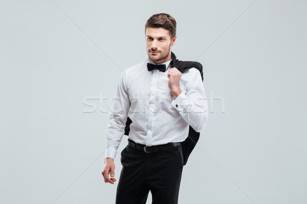 Handsome young man in tuxedo with bowtie holding his jacket Stock photo © deandrobot
