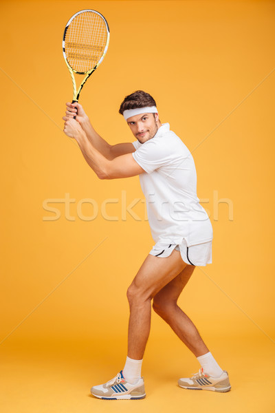 Full length of attractive man player standing and playing tennis Stock photo © deandrobot