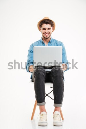 Smiling man in hat sitting on chair and using laptop Stock photo © deandrobot