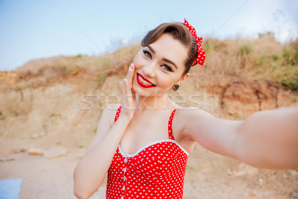 Smiling young cheerful pin up girl making selfie Stock photo © deandrobot
