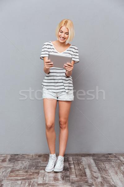 Derűs csinos fiatal nő áll tabletta szürke Stock fotó © deandrobot
