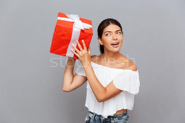 Jeune femme se demander quoi à l'intérieur présents Photo stock © deandrobot