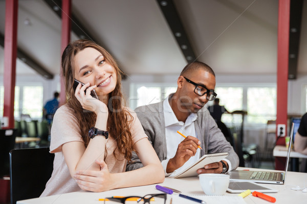 Cheerful business woman working with serious african man in office Stock photo © deandrobot