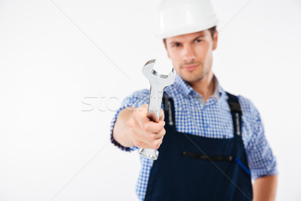 Close up portrait of a serious handsome builder holding wrench Stock photo © deandrobot