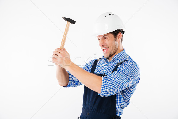Funny young builder applying hummer to his head in helmet Stock photo © deandrobot